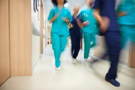 Doctors and nurses running through a hallway.