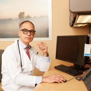 Photo of Nigel Girgrah, MD, in his medical office.