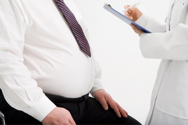 Physician standing in front of an obese man
