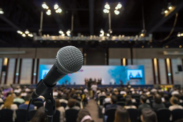 Photo of tight shot of microphone at podium in front of audience.