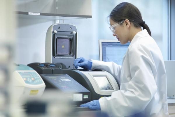 Woman in lab coat at testing machine