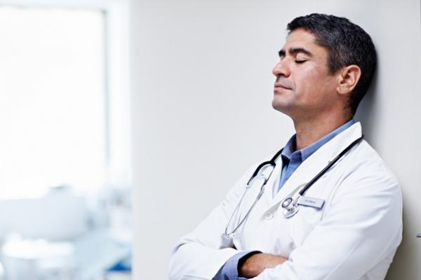 Tired physician leaning on a wall