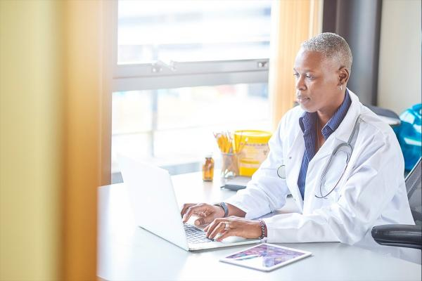 Physician sitting at desk working on laptop with iPad on the side.
