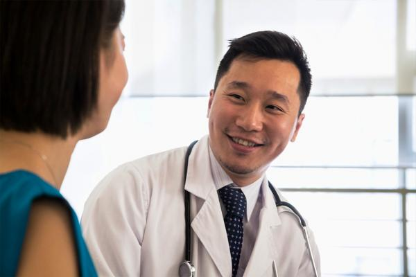 Smiling physician talking to patient.