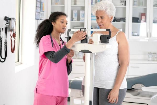 Woman being weighed in physician's office