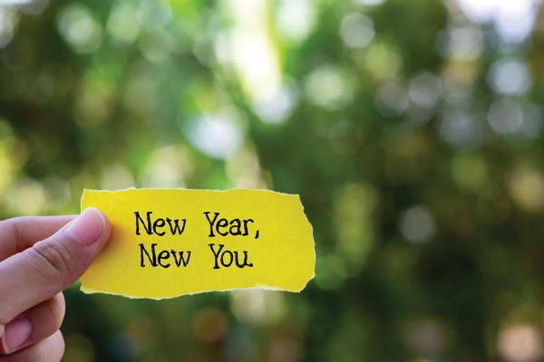 Hand holding a paper with the words New Year New You