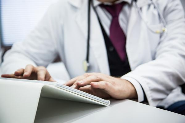 Physician typing on tablet
