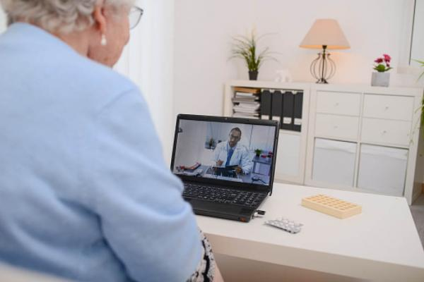 Older woman consulting with physician via computer-telehealth