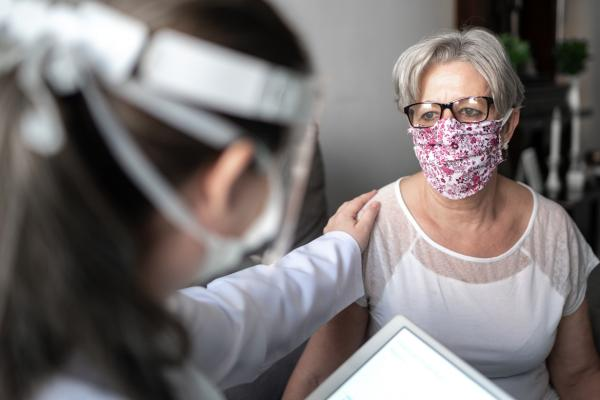 Patient in face mask with health care professional
