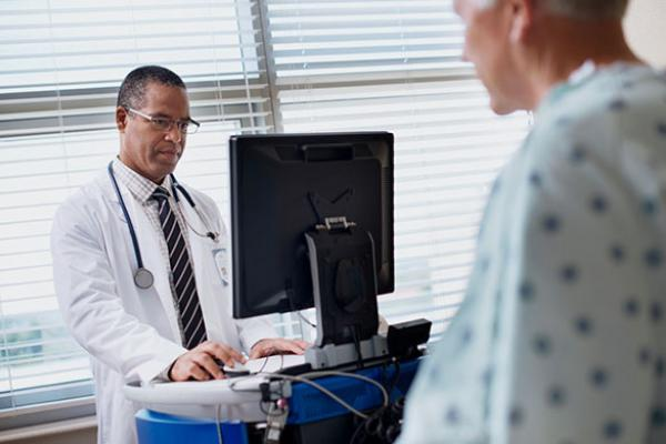 Doctor with computer consulting with patient