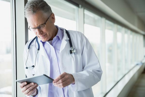 A physician stands in a window-lined hallway and looks at his tablet.