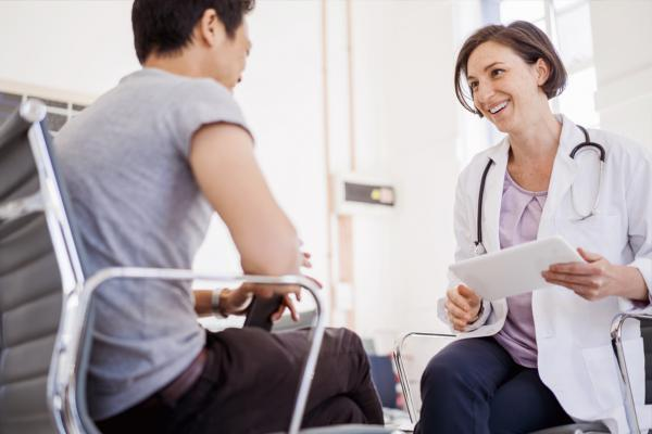 Smiling physician sitting down with patient