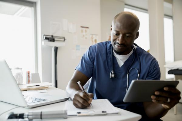 A male doctor in scrubs looks at PolicyFinder on his tablet.