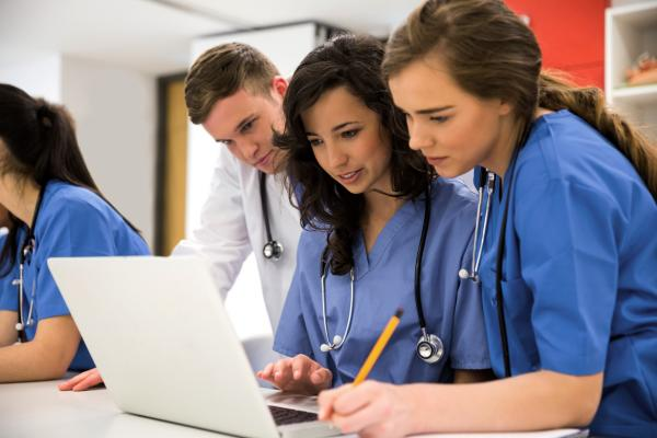 A diverse group of medical students gathers around a laptop to conduct research.
