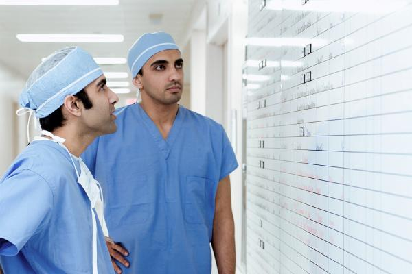 Two residents in surgical scrubs examine a whiteboard.