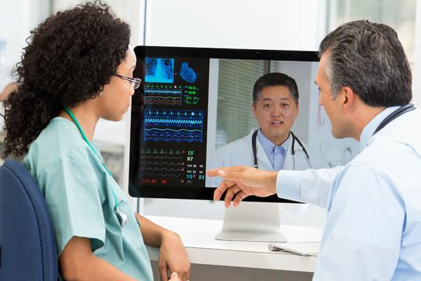 A male and female physician in front of a computer monitor.