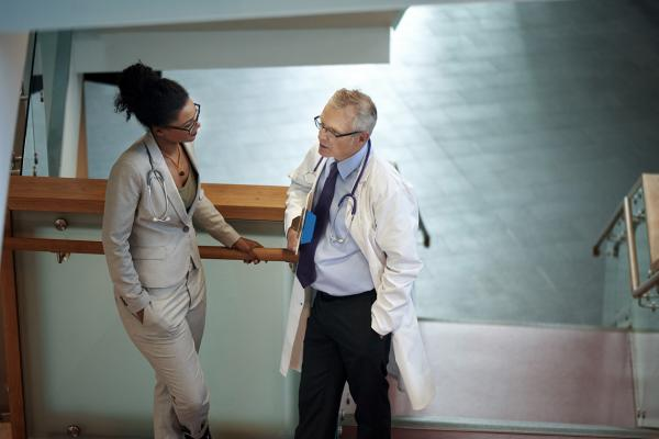 Male and female medical colleagues discuss medicare payment reform in the hallway.
