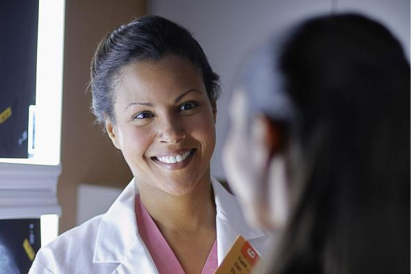 Close up of a female physician speaking to a younger female patient about diabetes prevention.
