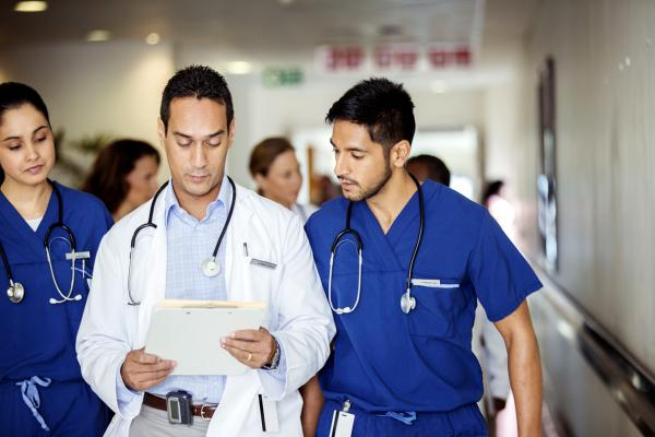 One female and two male residents walk down a hospital hallway examining a patient's health records.