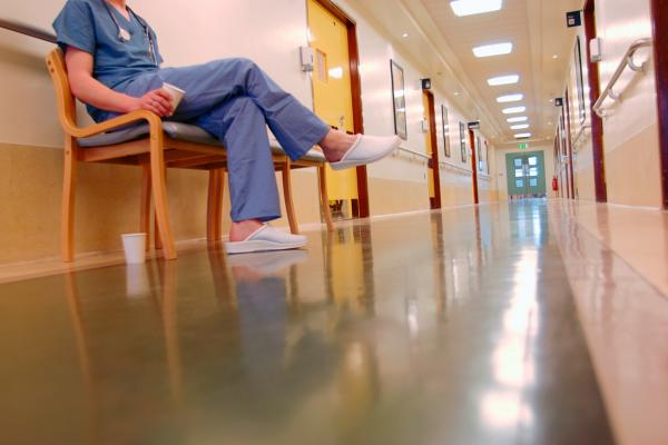Physician sits in a corridor with a cup of coffee in hand.
