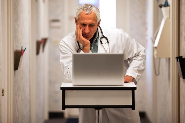A physician reads a laptop with his hand on his chin.