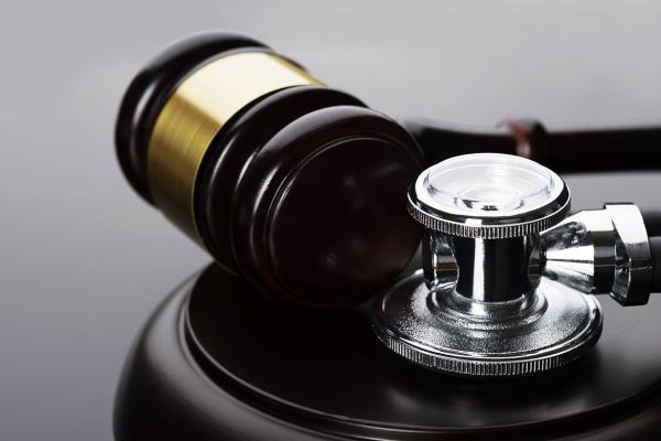 Close-up of gavel and scope resting on a desk.