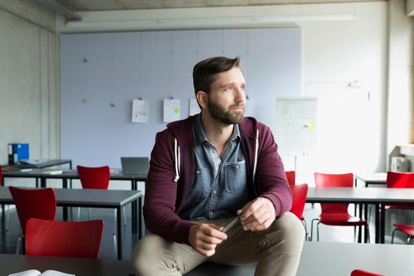 A man sitting on a table in an empty classroom holding a pen and looking out the window.