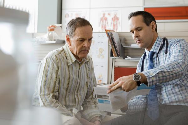 Physician explains information in medical pamphlet to patient.