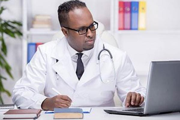 African American doctor sitting at a desk, looking at a laptop in the office.