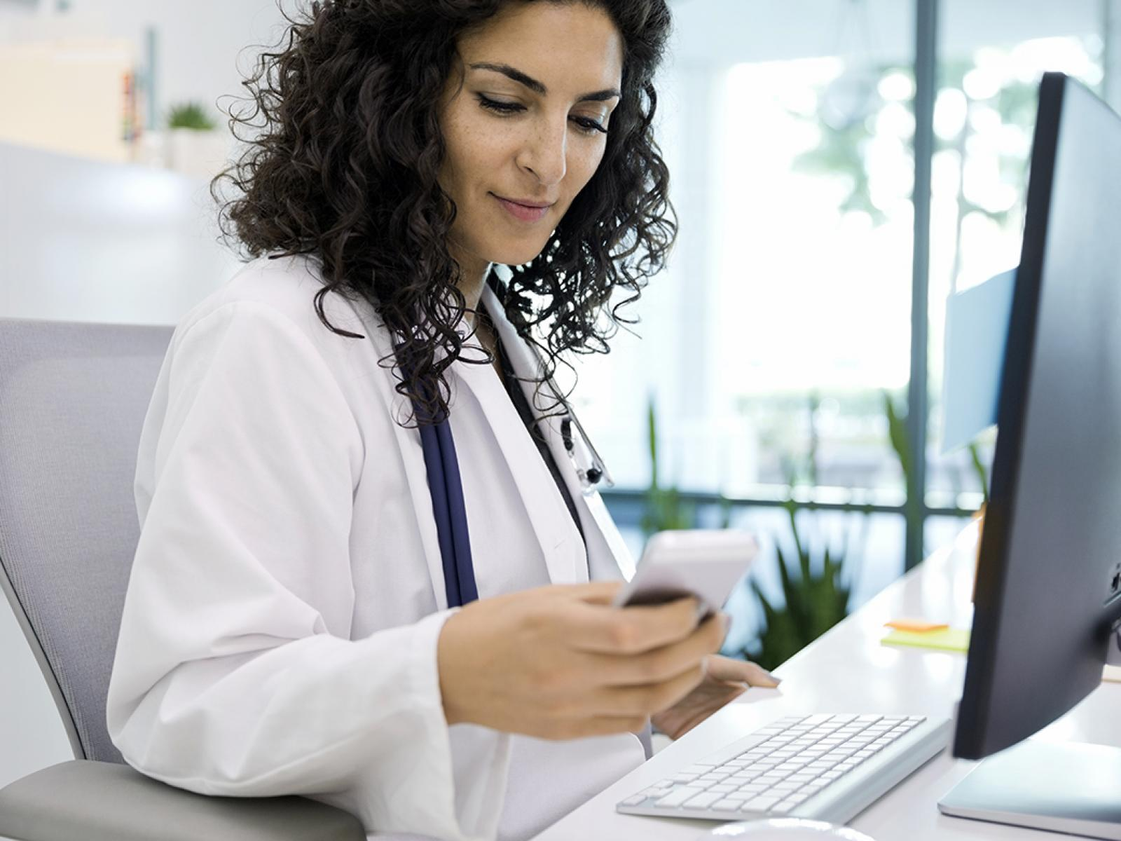Medical professional reviews information on cell phone.