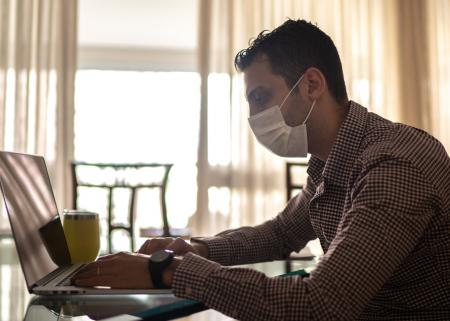Man wearing facemask and typing on laptop
