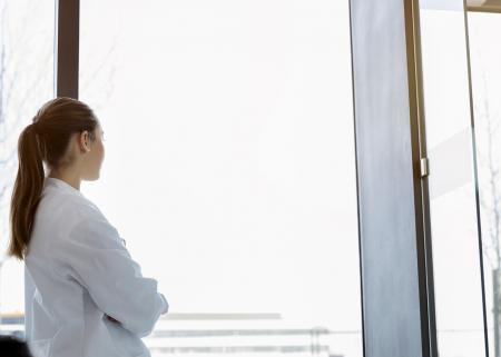 Woman in lab coat looking out window