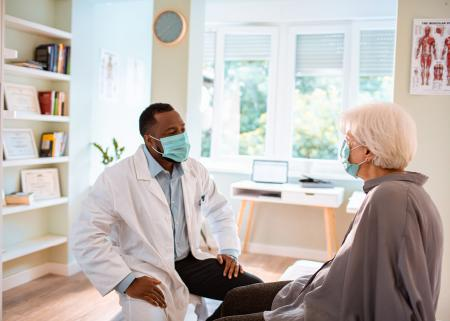 Physician and patient wearing face masks