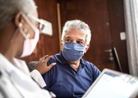 Doctor speaking to a Latinx patient, both wearing masks.