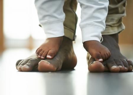 Close-up of an African-American parent's feet with their child's feet on top.