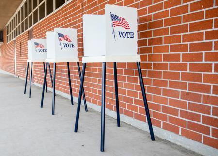 Three punch-tab style voting booths with an American flag and 'VOTE' on their sides, outdoors in front of a brick wall.