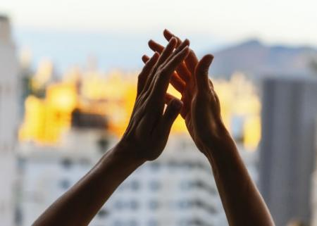 Hands raised in gratitude in front of window
