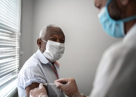 Elderly man receiving vaccine from physician