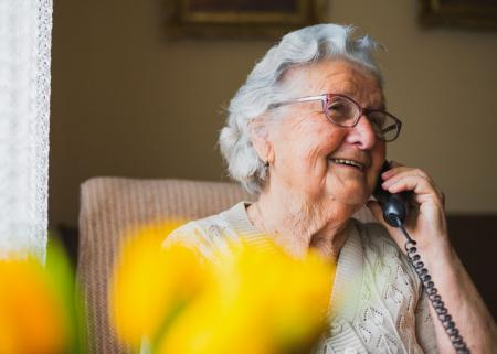 Smiling elderly person talking on the phone