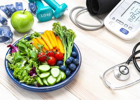 Clockwise, a measuring tape, apple, 1 kg hand weights, a BP monitor, a stethoscope and a plate of fruits and vegetables.