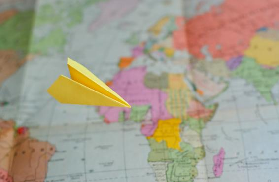 Map with a paper airplane flying in front of it