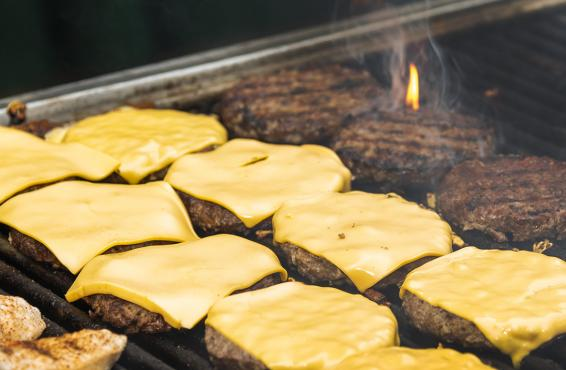 A photo of about 10 cheeseburgers cooking on a grill