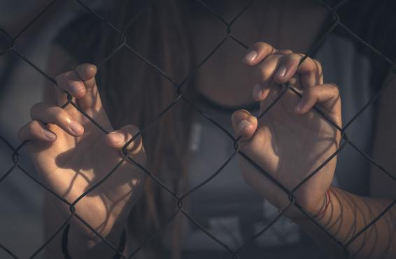 Woman standing behind a fence, holding on