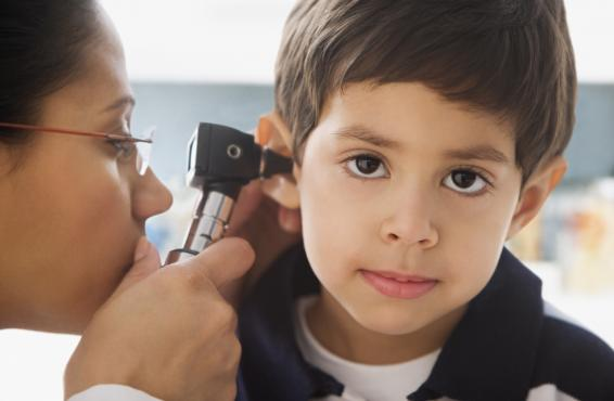 Doctor looking to child's ear with an otoscope