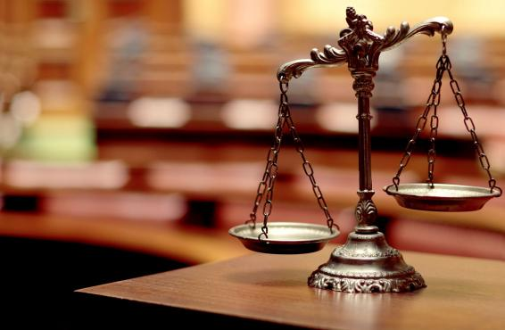 Scales of Justice on wooden table, courtroom blurred in the background