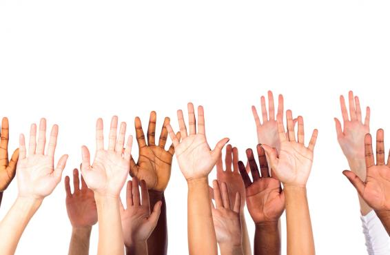 Group of people with hands raised to volunteer