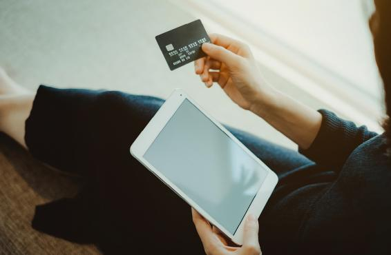 Person holding credit card and tablet computer