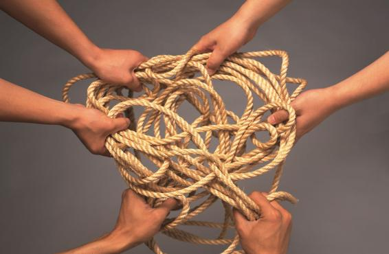 Multiple hands holding a tangled rope