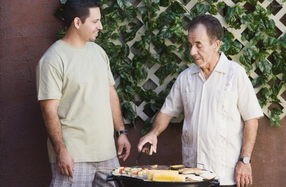 Two men standing at an outdoor grill