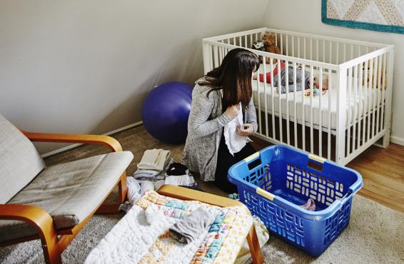 Mother folding clothes while baby sleeps in crib